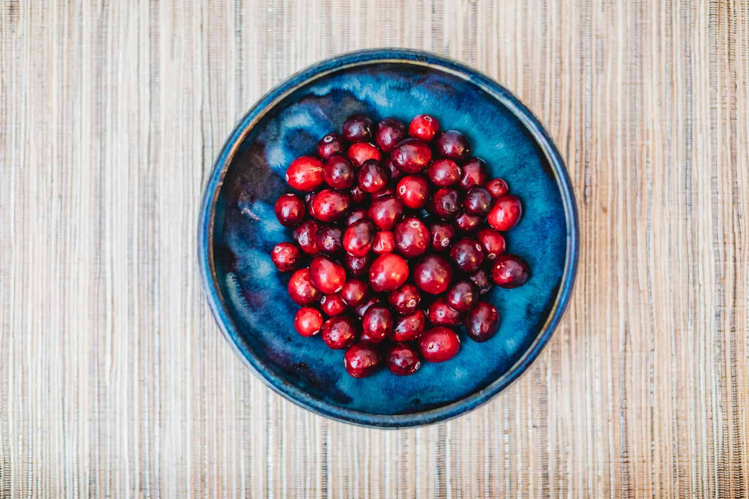 Ripe red cranberries in a blue bowl
