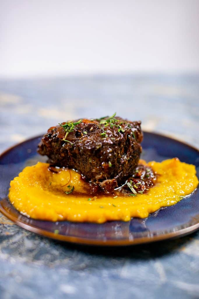 Prepared butternut squash puree recipe with braised meat on a plate