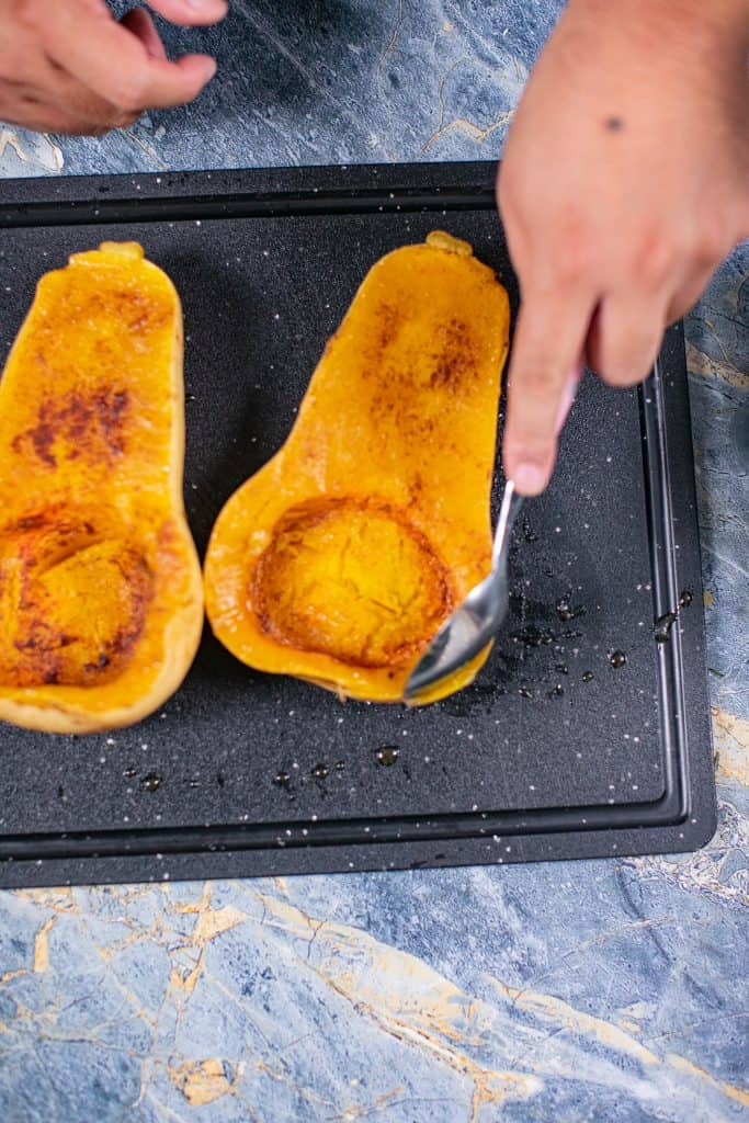 Person scooping out roasted butternut squash from pan