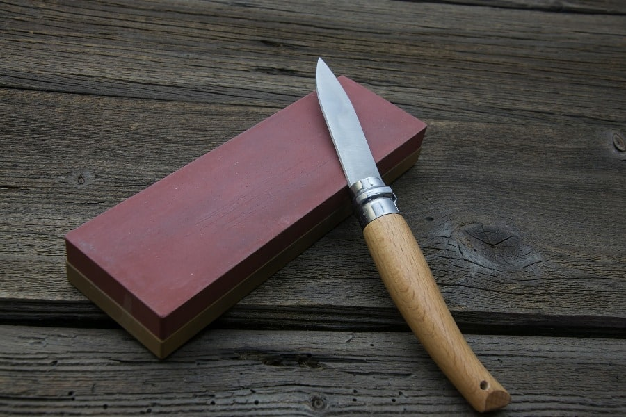 Used knife on top of a sharpening stone
