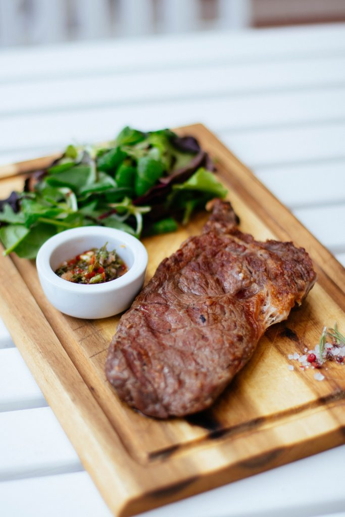 steak and vegetable on wooden plate