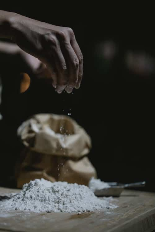 Prepping to dredge fish with a bag of flour