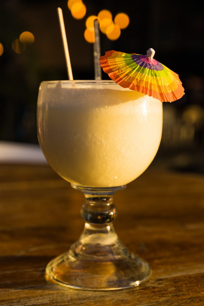 A pina colada in a wine glass with a small umbrella and a straw