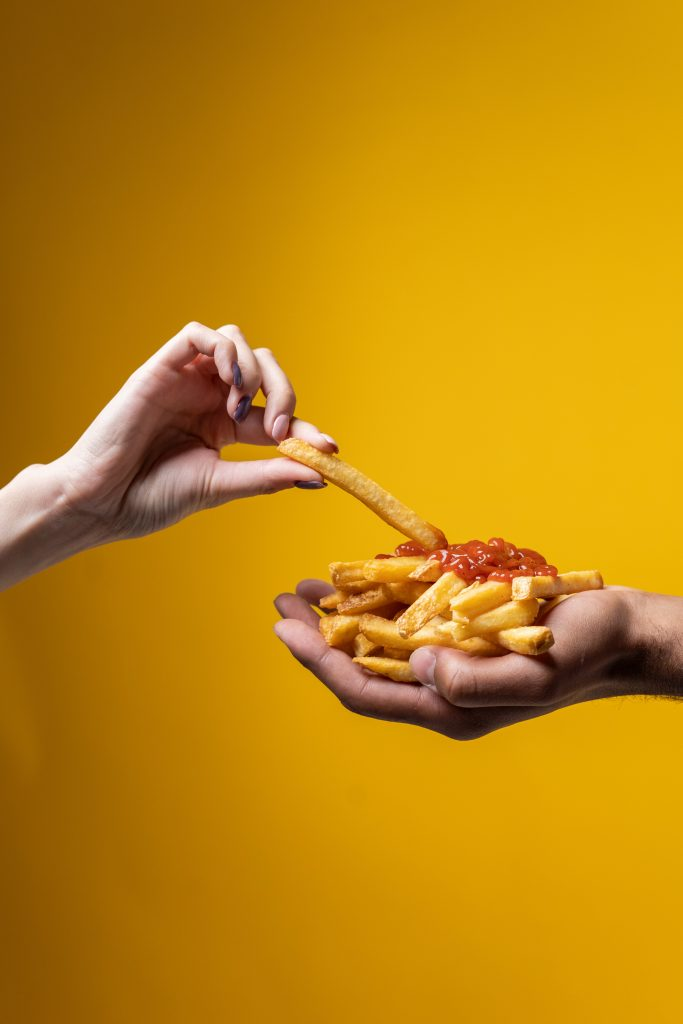 Hand dipping her french fries in ketchup