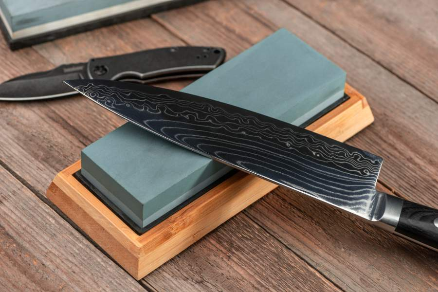 Knife and whetstone on a wooden table