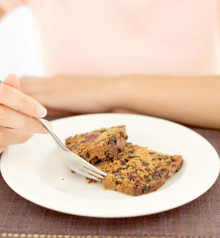 Woman eating a piece of fruitcake