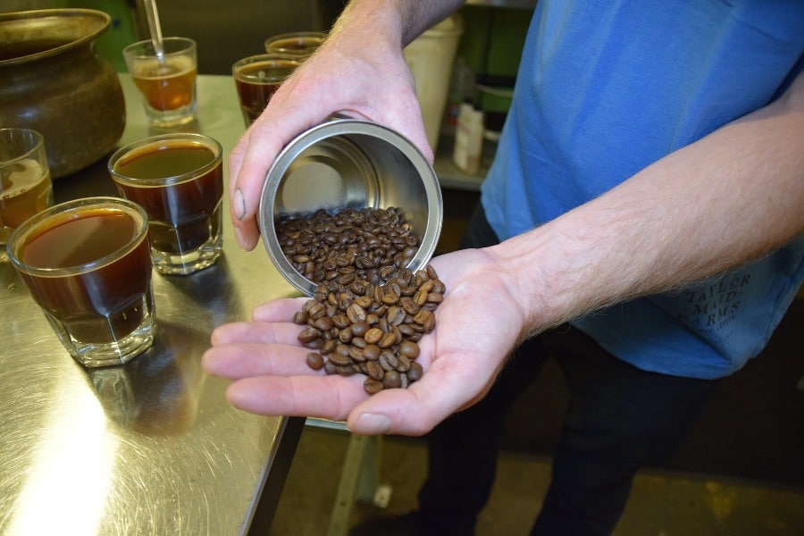 Man taking coffee beans out of a can