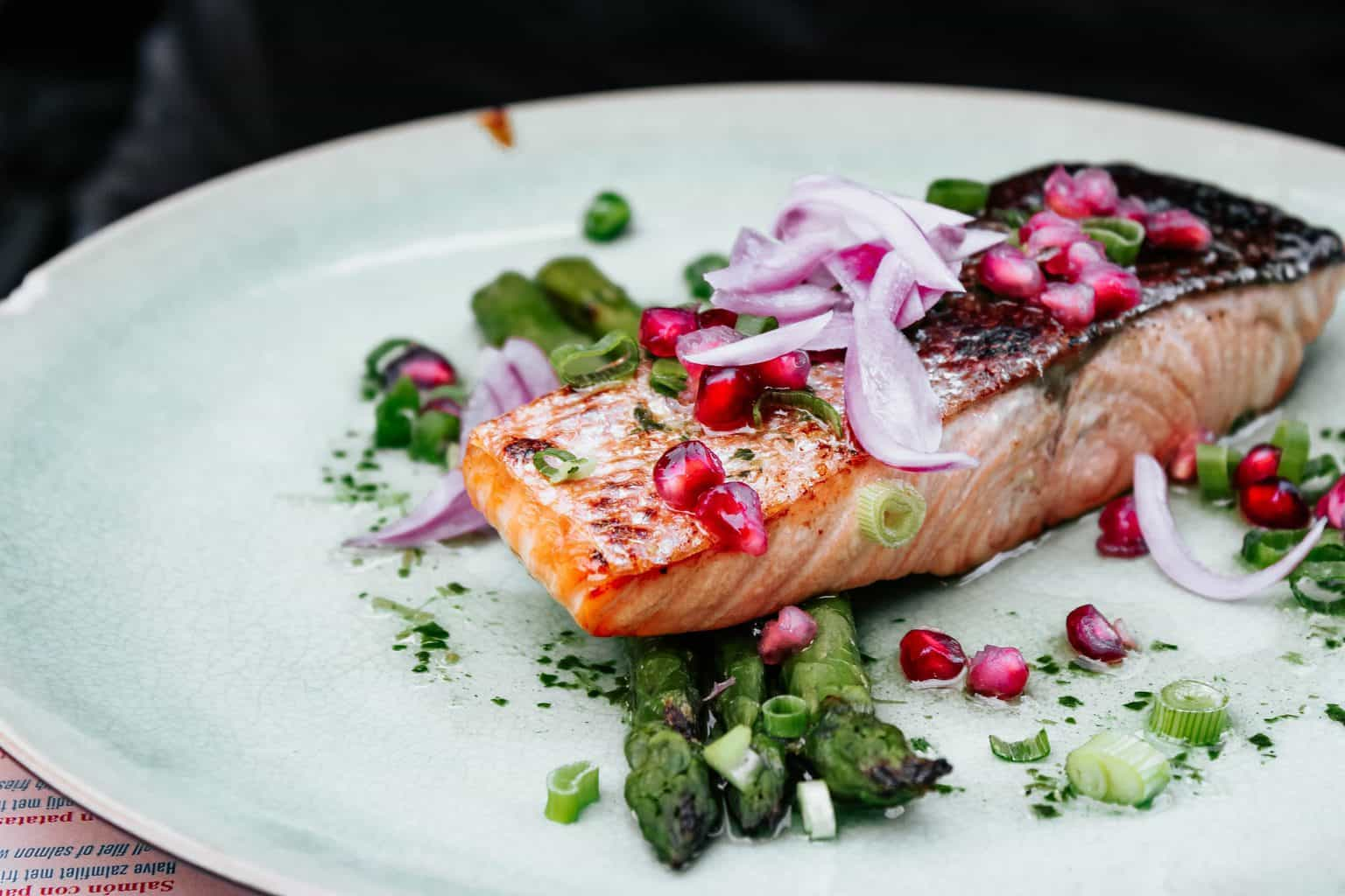 A cooked salmon with onions and asparagus