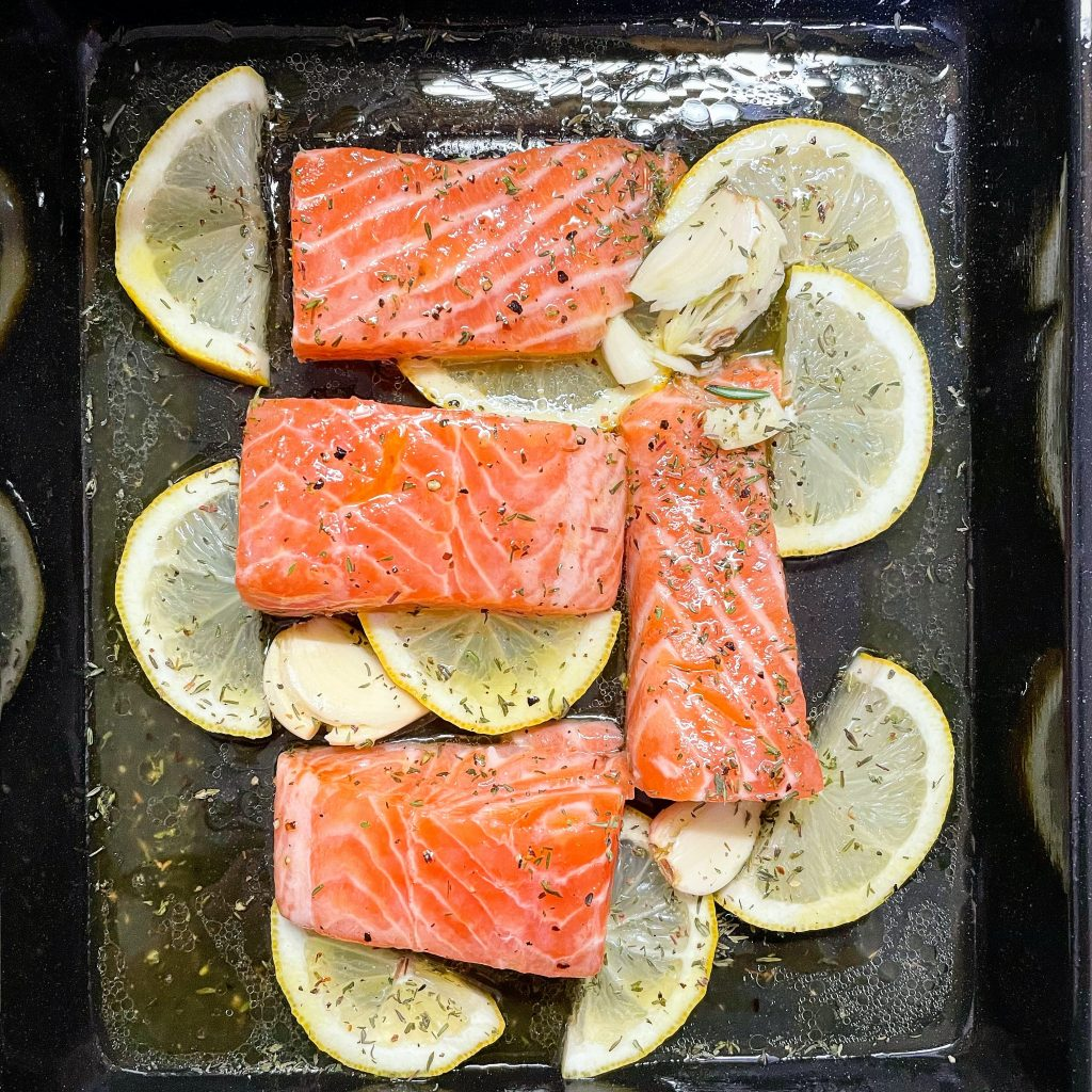 Four pieces of sliced salmons with sliced lemons