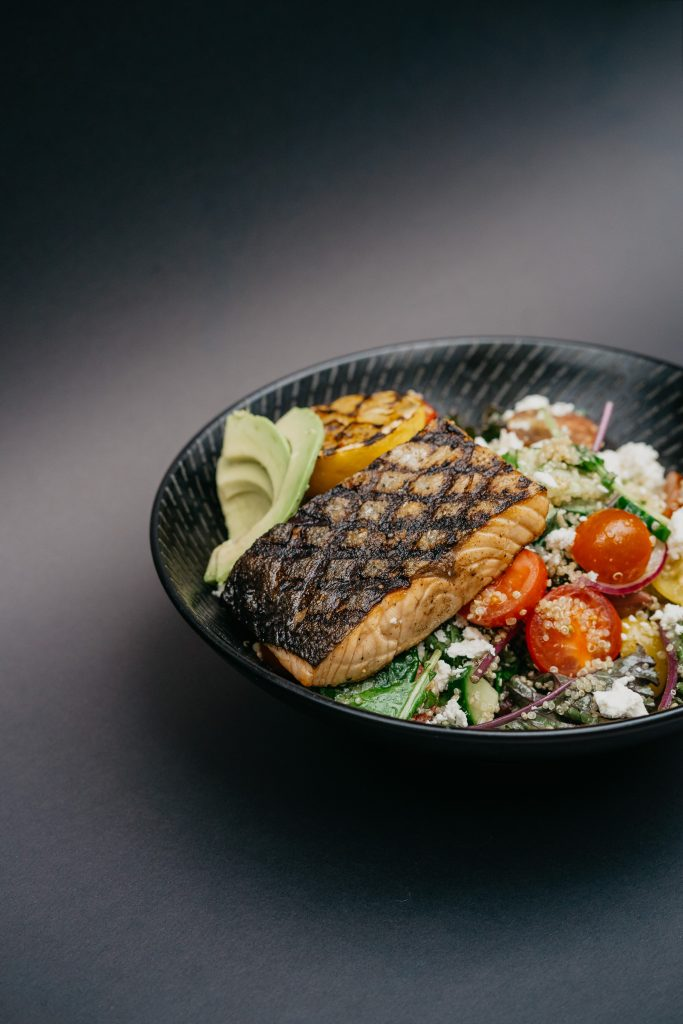 A salad meal with a salmon on top