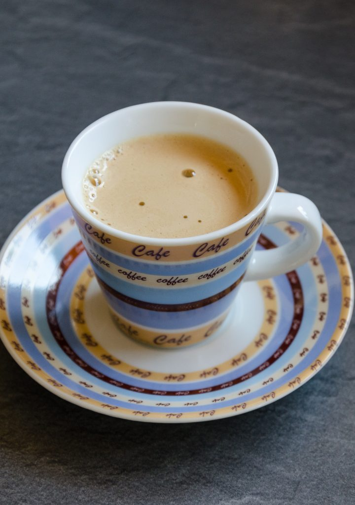 A cuban coffee served in a tea cup and plate