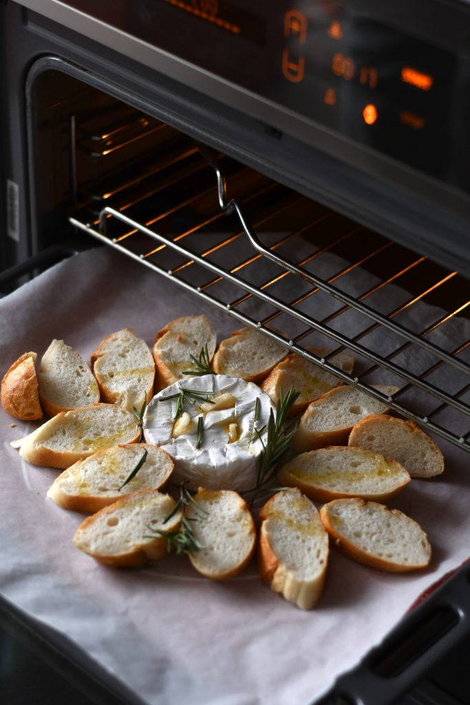 An open oven with goat cheese in the center of the pan with bits of bread