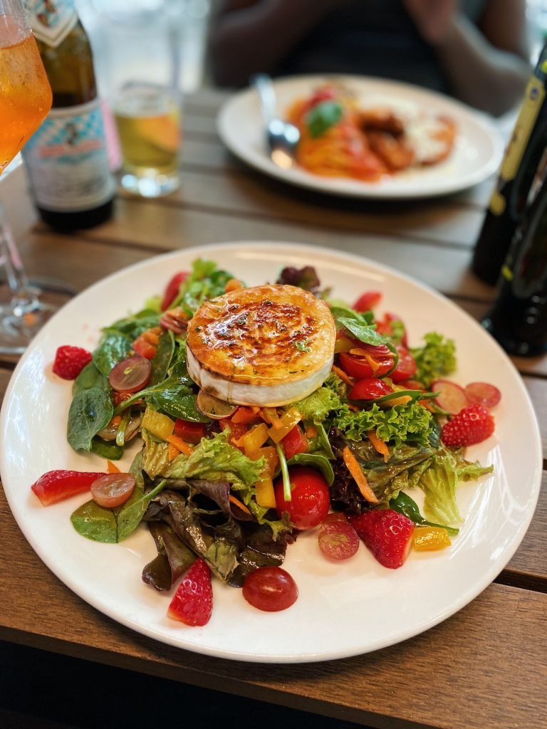 A vegetable salad meal with goat cheese on top