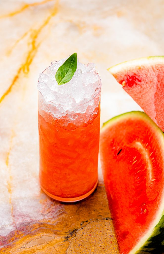 A watermelon and a glass of drink with leaf