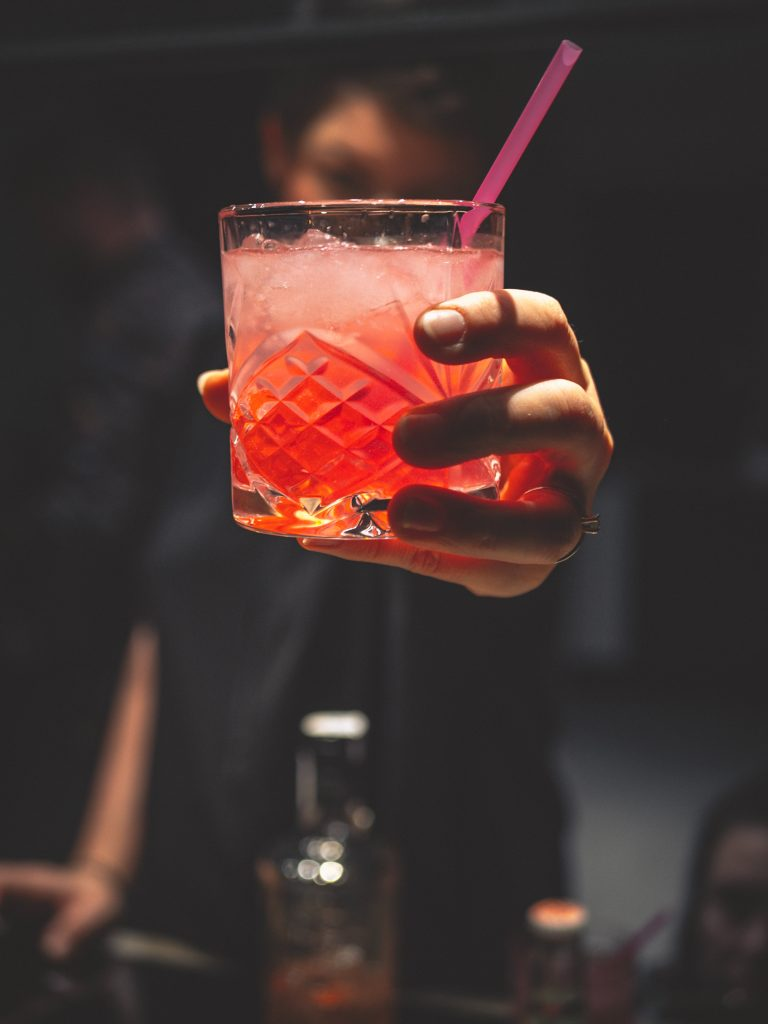 A person serving a glass of red drink with straw