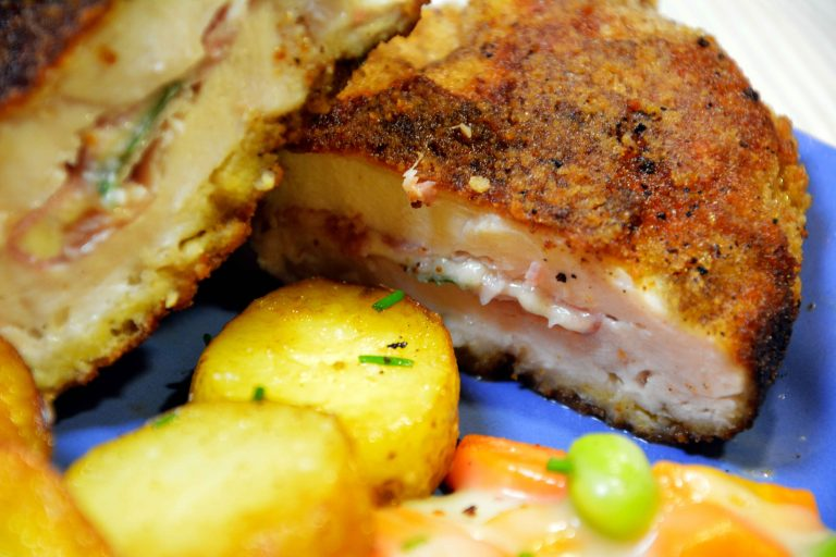 Close up shot of a sliced chicken cordon bleu with side dishes