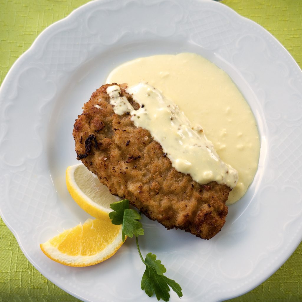 Chicken cordon bleu served on a plate with sliced lemon and white sauce