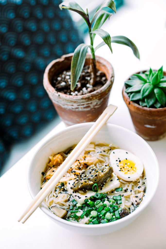 A noodle soup with egg and chopsticks near the plants