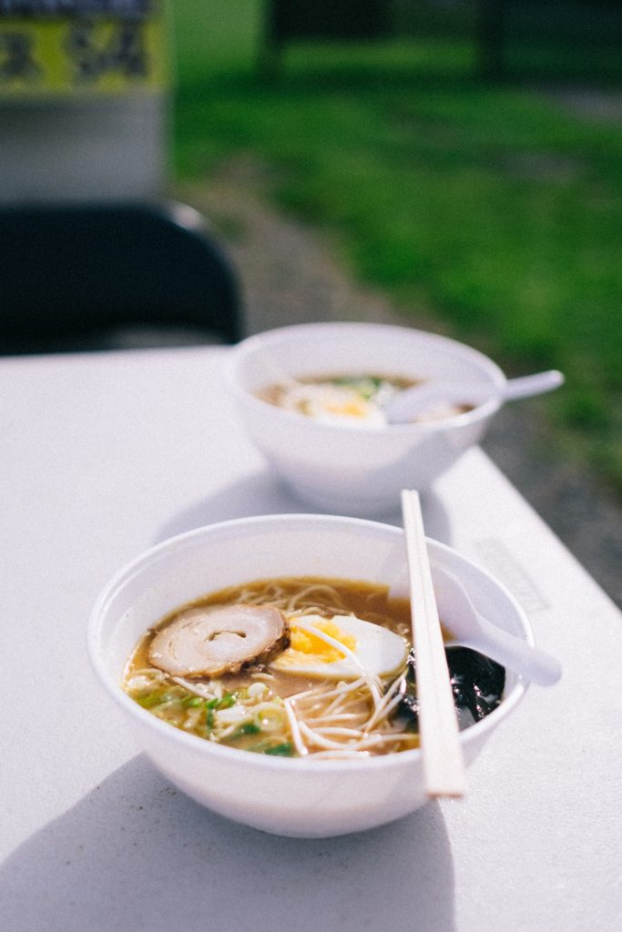 Two noodle soup bowls served outdoors with chopsticks